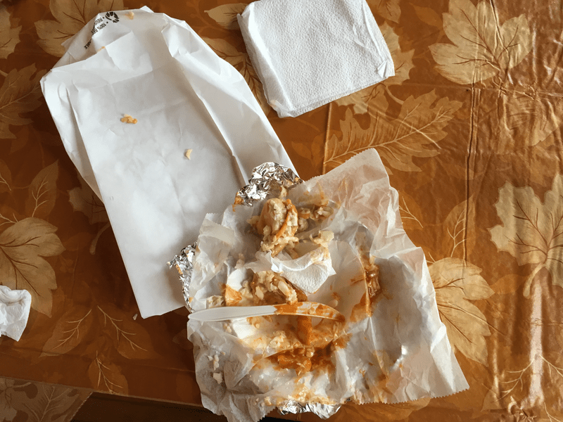 Remains of an eaten Polish boy, wrapper and napkins on a tabletop
